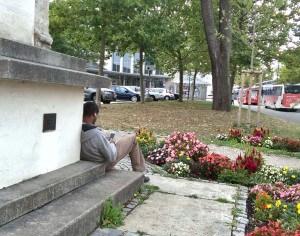 Refugee sitzt vor einem Denkmal und surft.